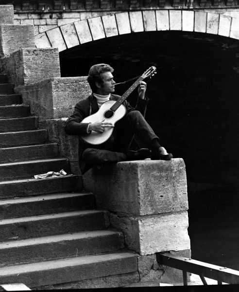 A young man playing his guitar near a bridge