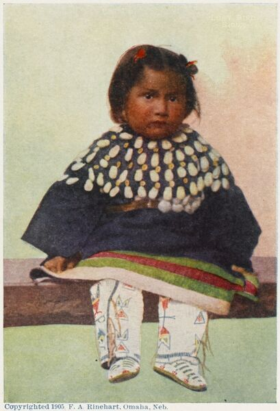 A very young Native American Toddler, wearing a shell-adroned shawl, fantastic patterned trousers and moccasins