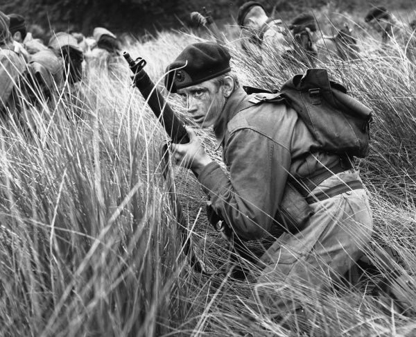 A group of young soldiers or cadets -- the one in the foreground holds a rifle and has a camouflaged face. Perhaps they are taking part in a training exercise or are on manoeuvres