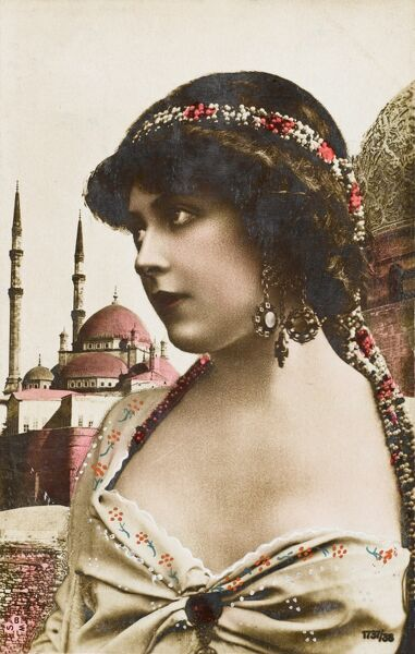 An attractive young Turkish girl in alluring attire with beads in her hair and large jewelled earrings, gazes out over the rooftops of the city of Constantinople