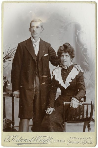 A young Victorian couple pose for their photograph in the studio. They are wearing their best clothes, perhaps for a wedding. He wears a long coat, a waistcoat and a wing collar with tie. She wears a dark dress with lacy white trimmings at the collar