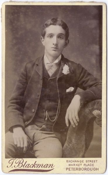 A young Victorian man in his best clothes, with a cravat and pin, and a flower in his buttonhole, poses in the photographer's studio