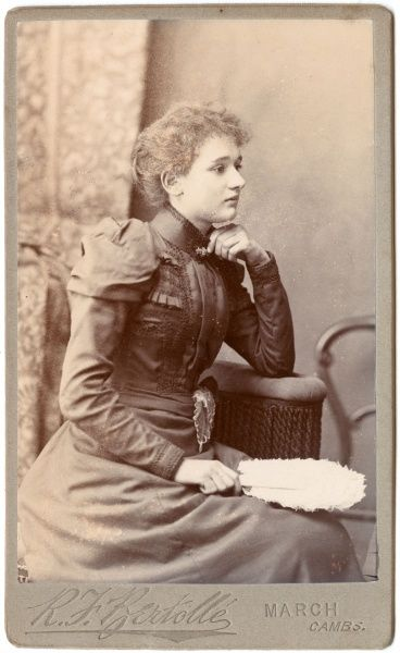A young Victorian woman poses in the photographer's studio, wearing a stylish dress with a high collar and embroidery on the bodice and cuffs. She is seated in profile, with a white feather fan in her hand