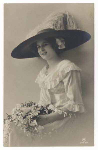 An attractive young woman wearing a wide-brimmed hat, posing with a bouquet of flowers