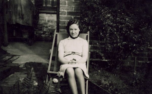 A young woman sitting in a deckchair in a back garden. Date: circa 1930s