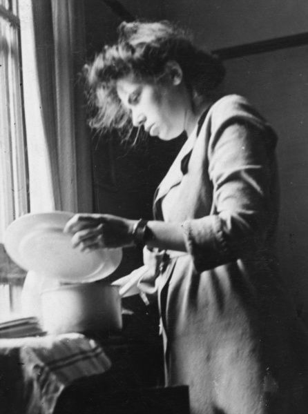 A young woman with slightly untidy hair doing the washing up, probably in wartime London