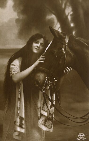 A stylish young woman tenderly holds the head of her favourite horse Date: circa 1906