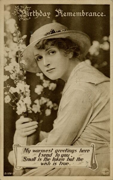 Birthday Remembrance -- a young woman posing with flowers on a birthday postcard. Date: early 20th century