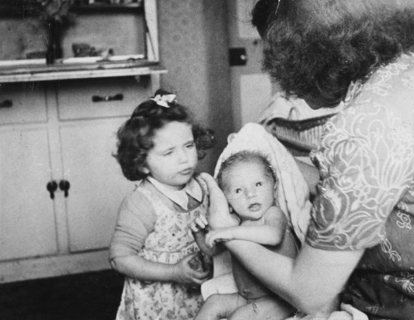 A young woman in a kitchen with her two children -- a girl of about four or five, and a baby. The baby has just had her bath and the woman is drying her with a towel