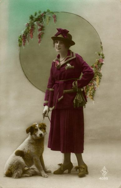 A pretty young woman in a smart purple costume, with her pet dog on a lead. Date: 1920