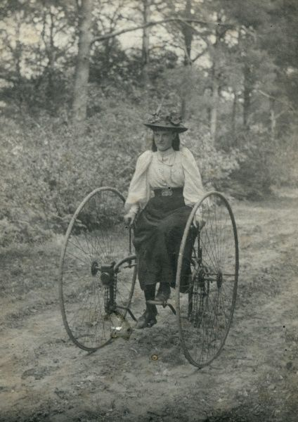 A young woman riding an early form of bicycle along a country lane. The wheels are large, and are placed on either side of the rider, who sits on a seat in the middle. Date: early 20th century