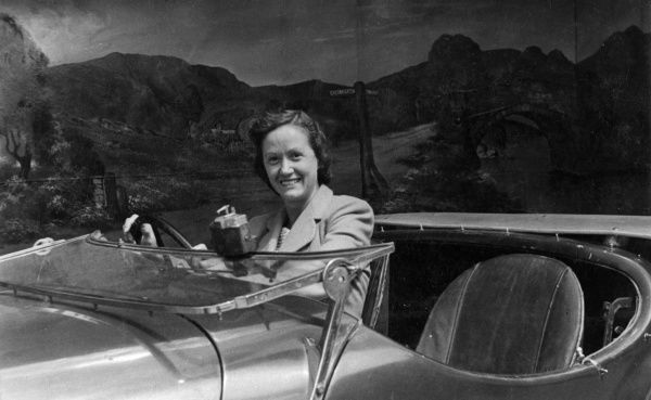 A young woman poses at the wheel of an open-topped car in the photographer's studio. Date: late 1940s