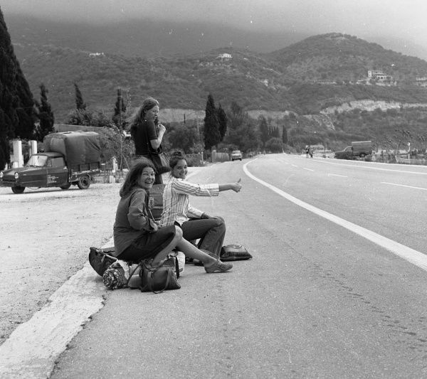 Three young women hitch-hiking from the side of a road in Ipsos, Corfu, Greece