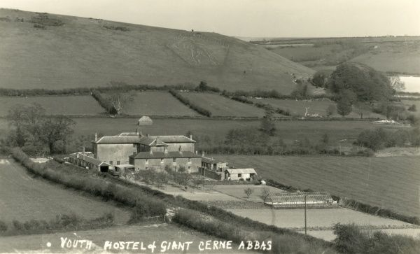 Distant view of the youth hostel at Cerne Abbas, Dorset. At the rear is the Cerne Abbas Giant carved into the hillside in chalk. The hostel, on Sherborne Road, was originally built in in 1836-7 as the Cerne Union workhouse, designed by Charles Wallis