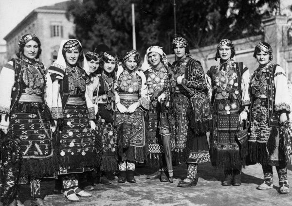 Beauties of Zara, Italy, wearing their elaborate traditional costumes and quaint caps, covered in gold coins. Date: 1930s