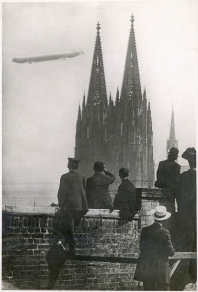 Excited spectators watching a Zeppelin Z111 fly over Cologne Cathedral, Germany