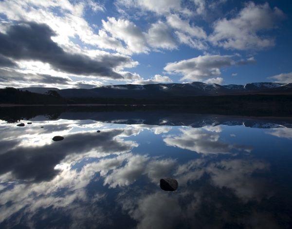 Scotland, Scottish Highlands, Cairngorms National Park. Dramatic clouds and Cairngorm mountains reflected upon the still face of Loch Morlich