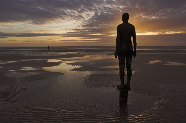 Another Place statues by artist Antony Gormley on Crosby beach, Merseyside, England, United Kingdom, Europe