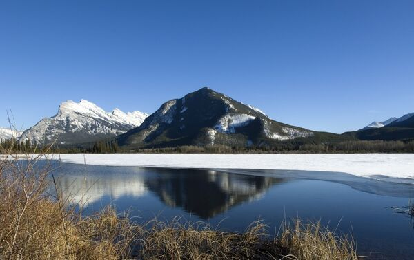 Reflection of Rocky Mountains in Vermilion Lakes in Banff National Park