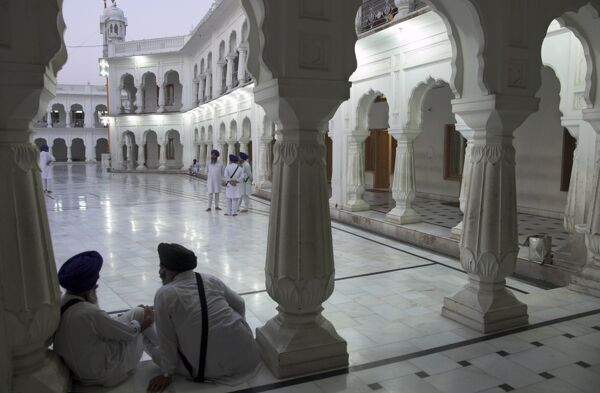 Two Sikhs priests at dawn sitting under arcades, Golden Temple, Amritsar, Punjab state, India, Asia