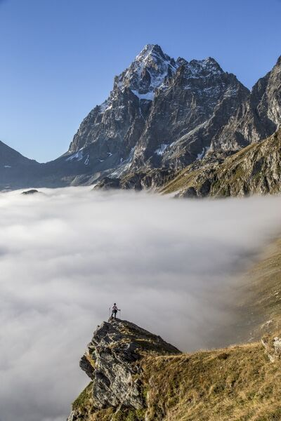 A solitary hiker admiring the profile of the Monviso (Monte Viso) emerging from the fog, Piedmont, Italy, Europe