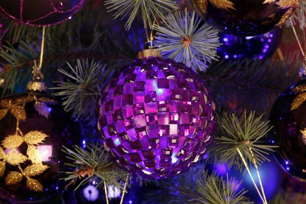 purple baubles and christmas decorations with lights on a xmas tree