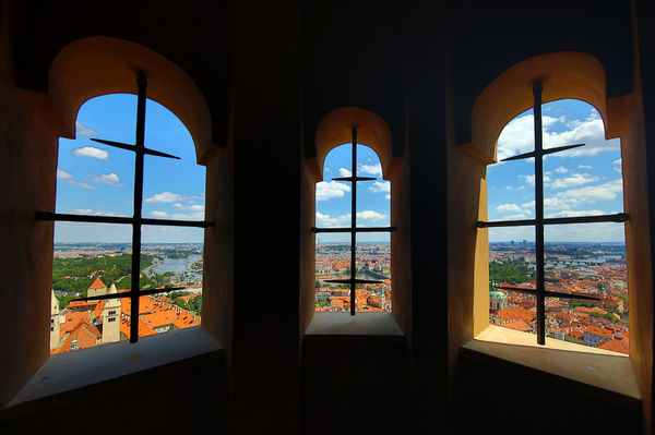General city skyline view of Prague and the Vtlava River seen through an arched window of St Vitus Cathedral, Czech Republic