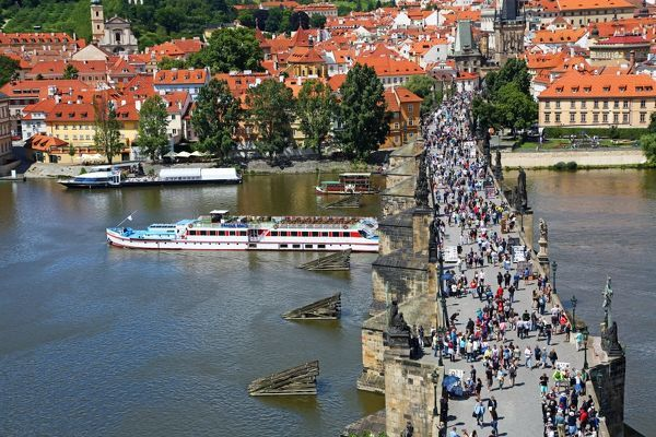 Tourists walking over the Charles Bridge over the Vltava River with a boat sailig under it in Prague, Czech Republic