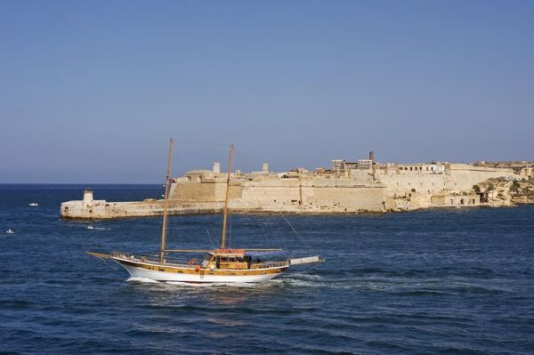 Malta, Valletta. A fishing boat motors out of the entrance to the Grand Harbour past Ricasoli Point