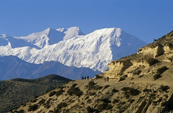 Nepal, Himalaya, Mustang. Trekkers on the main Mustang trail with the Annapurna massif soaring on the horizon behind