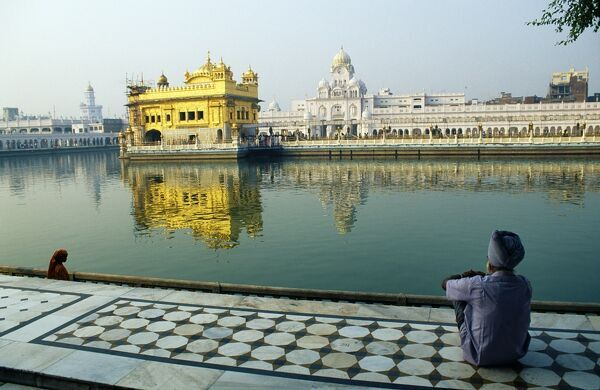 A Sikh pilgrim pauses for reflection by Amrit Sarovar, the Pool of Immortality-Giving Nectar, and the Golden Temple. India, Punjab, Amritsar. A Sikh pilgrim pauses for reflection by Amrit Sarovar, the 'Pool of Immortality-Giving Nectar', a