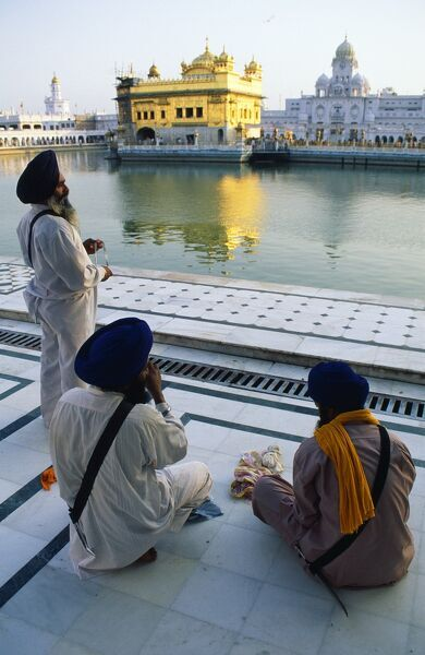 Silk pilgrims pause beside the Amrit Sarovar, the pool of Immortality-Giving Nectar, and the Golden Temple. India, Punjab, Amritsar. Silk pilgrims pause beside the Amrit Sarovar, the 'pool of Immortality-Giving Nectar', and the Golden Temp