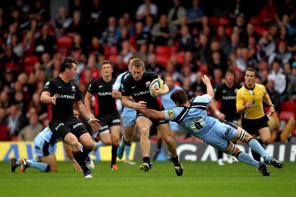 Saracens' Andy Saull is tackled by Newcastle's Ally Hogg