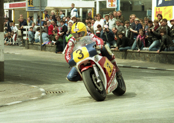 A packed audience watches Joey Dunlop take his Honda round Parliament Square in the 1984 Senior TT