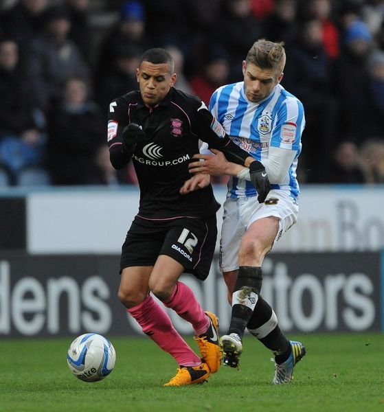 Huddersfield Town's Adam Clayton (right) and Birmingham City's Ravel Morrison (left) battle for the ball during the npower Football League Championship match at the John Smith's Stadium, Huddersfield