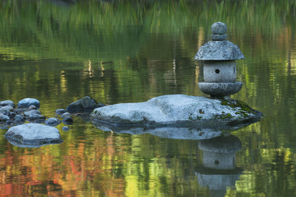 Concrete lantern on a rock in a pond surrounded by reflections of Fall colors in the water, Japanese Garden, Washington Park Arboretum, Seattle, Washington State