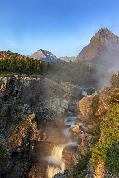 Swift current Falls at sunrise in Glacier National Park, Montana, USA