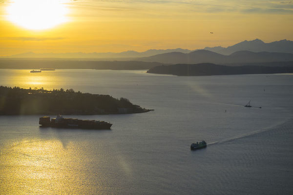 United States, Washington, Seattle. A Washington State ferry crosses Puget Sound near Seattle, sunset. A container ship passes West Seattle on the left, and Olympic Mtns in the background