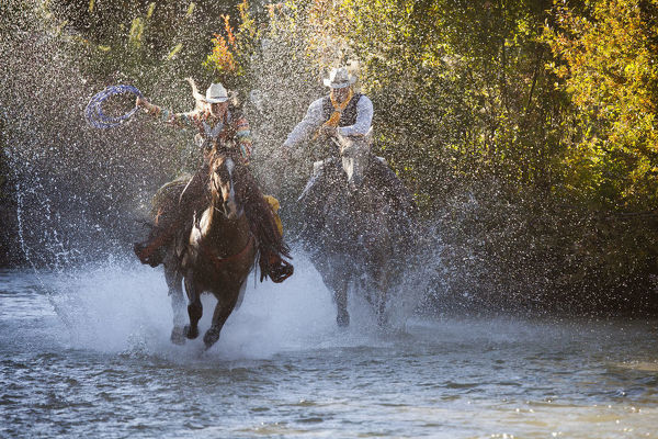 USA, Wyoming, Shell, The Hideout Ranch, Cowboy and Cowgirl on Horseback Running through the River (MR/PR)