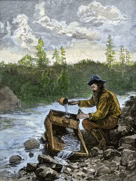 Prospector washing pebbles from a stream using a cradle device to sparate gold nuggets. Hand-colored woodcut of a 19th century illustration