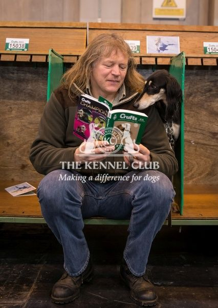 General shot of dog reading Crufts guide with handler