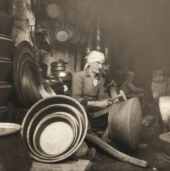 ISRAEL: METAL WORKERS, 1938.  Coppersmith at Nazareth, Israel, hammering out a 'dist.' Photograph by John D. Whiting, 1938