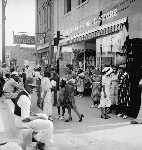 MAIN STREET SHOPPERS, 1939. African American men and women shopping and socializing
