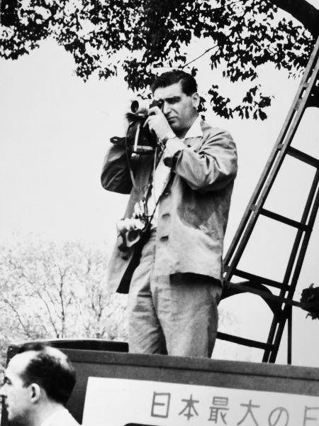 ROBERT CAPA (1913-1954).  Hungarian-born American war photographer. Capa photographing a May Day demonstration in Tokyo, 1954
