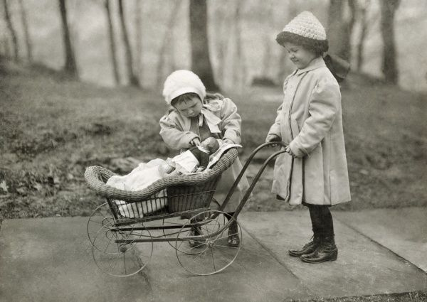 HINE: CHILDREN, 1912.  Two young girls playing with a Campbell Kid Doll and a baby carriage in New York City. Photograph by Lewis Hine, March 1912