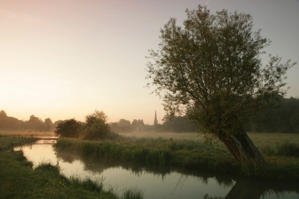 Early morning as the sun comes up over the river Windrush at Burford Oxfordshire