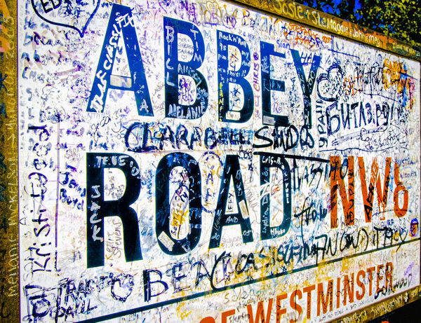 Famous Abbey Road road sign covered with grafitti from Beatle fans