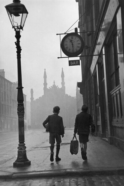 31st January 1948: Two boys walking along a street in the run-down Gorbals area of Glasgow. The Gorbals tenements were built quickly and cheaply in the 1840s, providing housing for Glasgow's burgeoning population of industrial workers