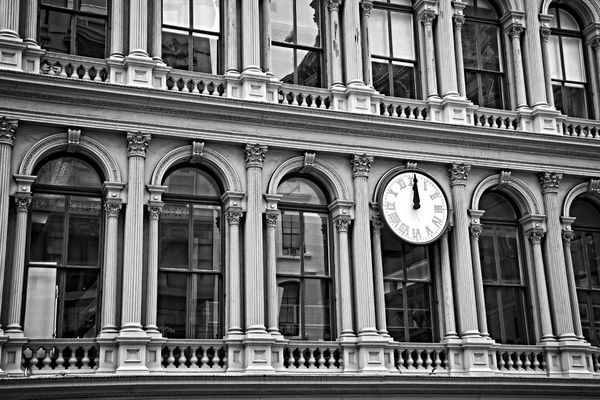 Old art deco office building in 5th Avenue, in New York City, near the Soho, with a big clock indicating it is noon