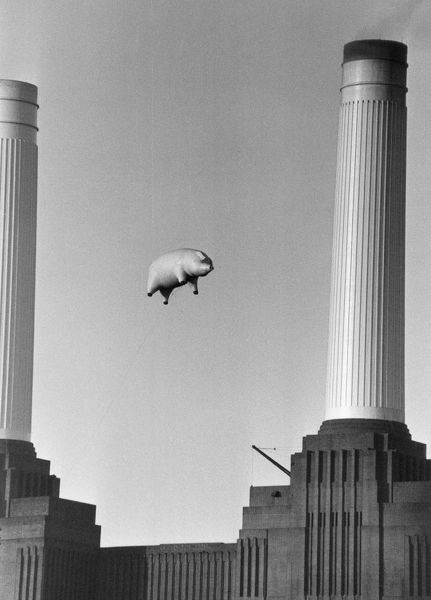 A 40-foot long inflatable pig suspended between two of the chimneys at Battersea Power Station, London, during a photoshoot for the cover of Pink Floyd's album 'Animals', 6th November 1976